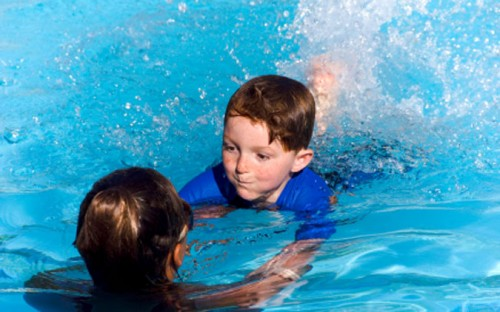 child and adult learning to swim