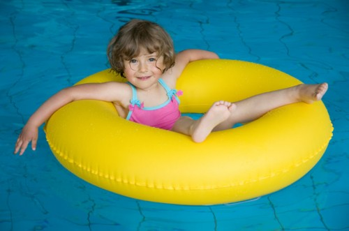 girl floating in yellow inner tube